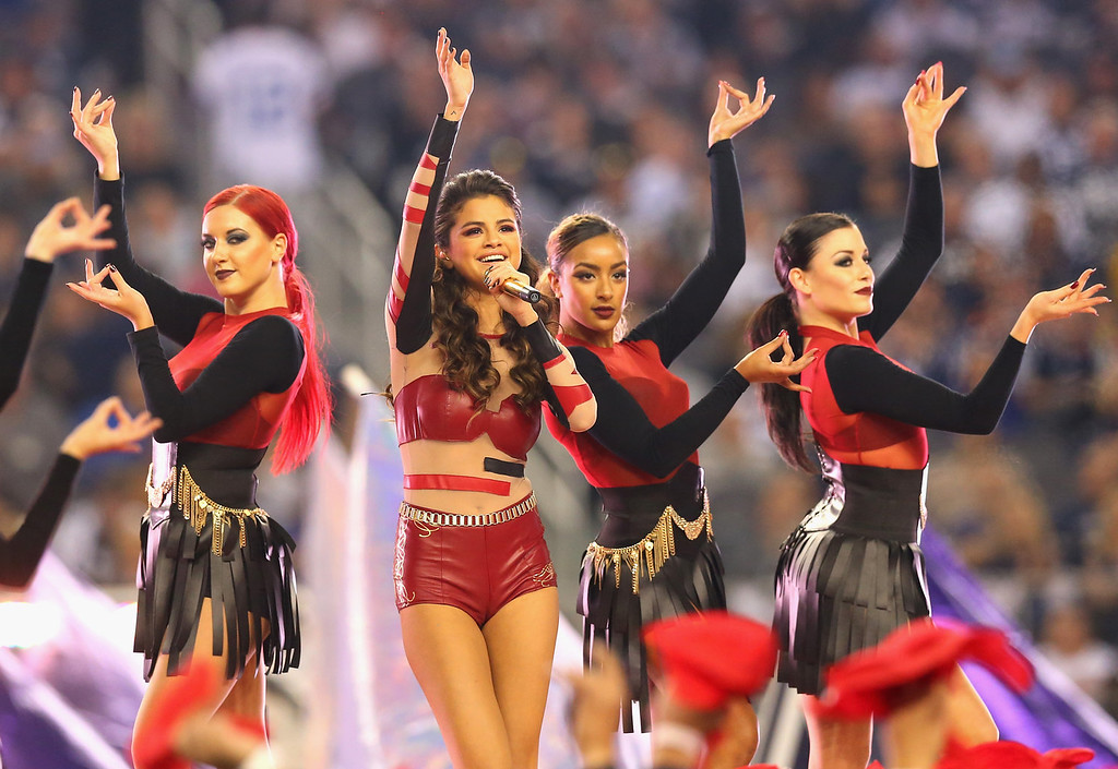 Description of . Selena Gomez performs during the halftime of a Thanksgiving Day game between the Oakland Raiders and the Dallas Cowboys at AT&T Stadium on November 28, 2013 in Arlington, Texas.  (Photo by Ronald Martinez/Getty Images)