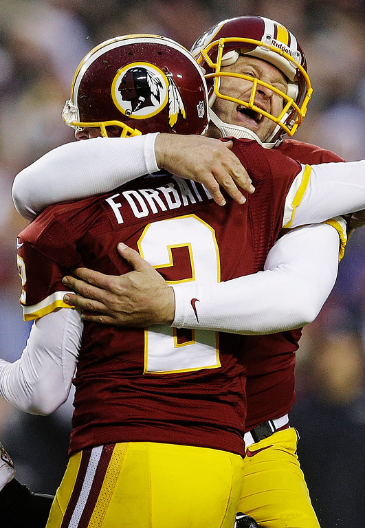 Description of . Washington Redskins' Sav Rocca, right, hugs Kai Forbath (2) after Forbath's winning 34-yard field goal in overtime of an NFL football game against the Baltimore Ravens in Landover, Md., Sunday, Dec. 9, 2012. The Redskins won 31-28. (AP Photo/Patrick Semansky)