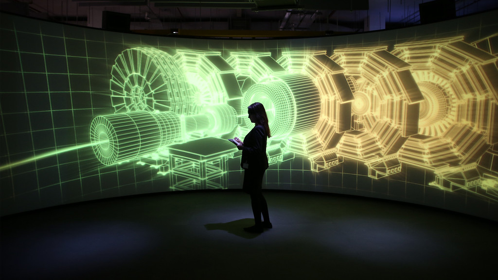 Description of . An employee of the Science Museum stands in front of a video projection showing the workings of the Large Hadron Collider (LHC)  at the 'Collider' exhibition on November 12, 2013 in London, England.   (Photo by Peter Macdiarmid/Getty Images)