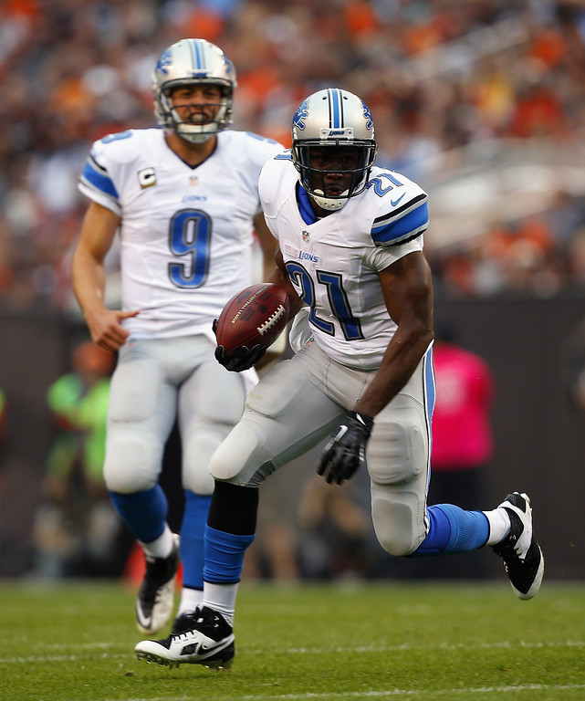 Description of . Running back Reggie Bush #21 of the Detroit Lions runs the ball as quarterback Matthew Stafford #9 watches during a game against the Cleveland Browns at FirstEnergy Stadium on October 13, 2013 in Cleveland, Ohio.  (Photo by Matt Sullivan/Getty Images)