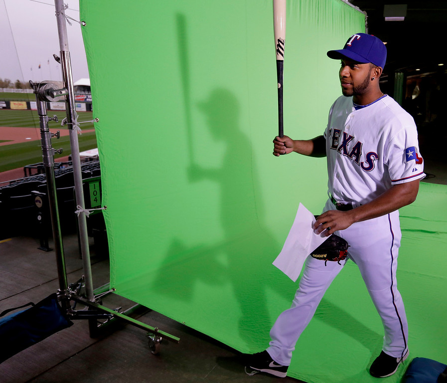 Description of . Texas Rangers shortstop Elvis Andrus walks between stations during photo day at baseball spring training  Wednesday, Feb. 20, 2013, in Surprise, Ariz. (AP Photo/Charlie Riedel)