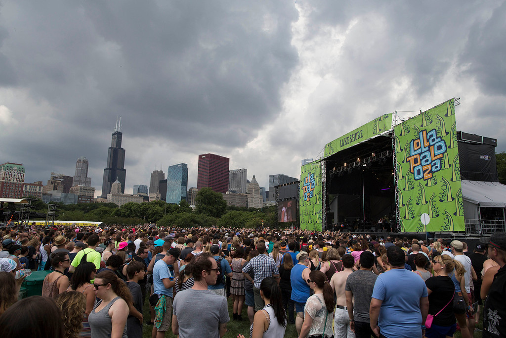 Description of . The Chicago skyline behind the Lollapalooza Festival while a rainstorm approaches in Chicago, Friday, Aug. 2, 2013.  (AP Photo/Scott Eisen)