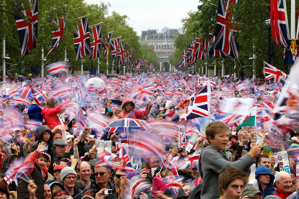 . n this June 5, 2012 file photo, revelers on the Mall in London watch Britain Queen Elizabeth II appear on the Buckingham Palace balcony as part of a four-day Diamond Jubilee celebration to mark the 60th anniversary of  Queen Elizabeth II accession to the throne. (AP Photo/Sang Tan, File)