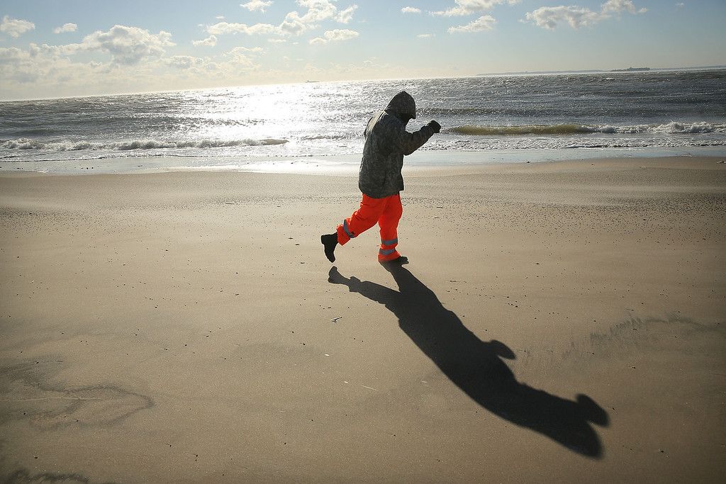 Description of . A runner jogs on a stretch of beach at Coney Island during subzero cold weather on January 7, 2014 in the Brooklyn borough of New York City. A