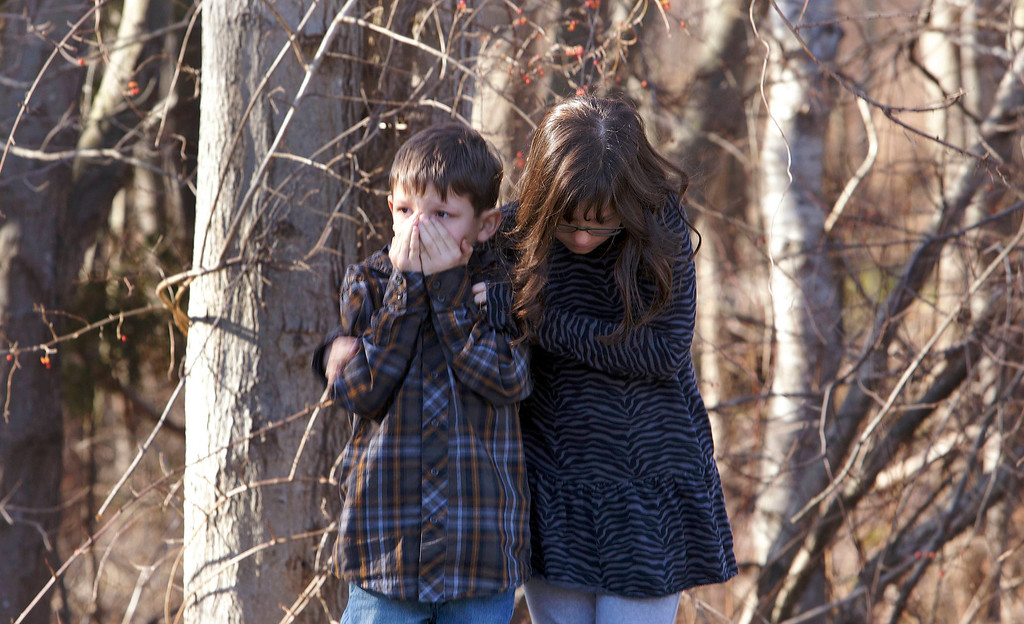 Description of . Young children wait outside Sandy Hook Elementary School after a shooting in Newtown, Connecticut, December 14, 2012. A shooter opened fire at the elementary school in Newtown, Connecticut, on Friday, killing several people including children, the Hartford Courant newspaper reported. REUTERS/Michelle McLoughlin