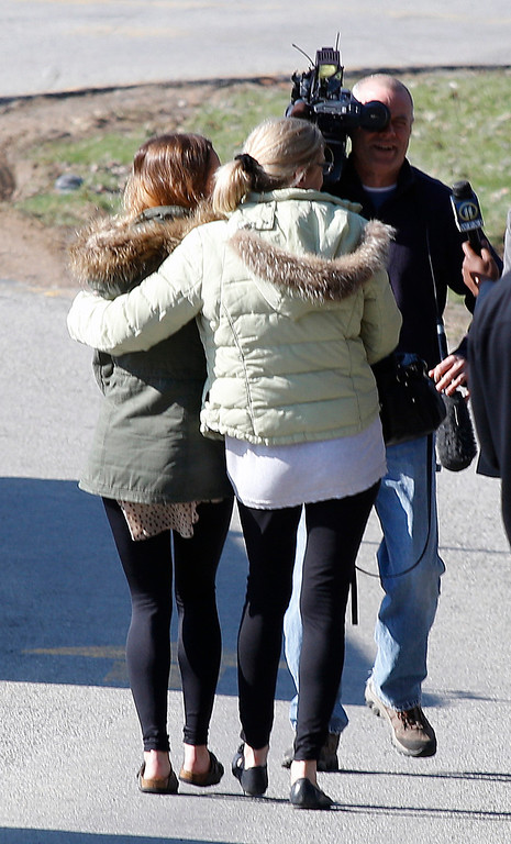 Description of . A pair of women walk arm-in-arm off the campus of the Franklin Regional School District, where several people were stabbed at Franklin Regional High School on Wednesday, April 9, 2014, in Murrysville, Pa., near Pittsburgh. The suspect, a male student, was taken into custody and being questioned. (AP Photo/Keith Srakocic)