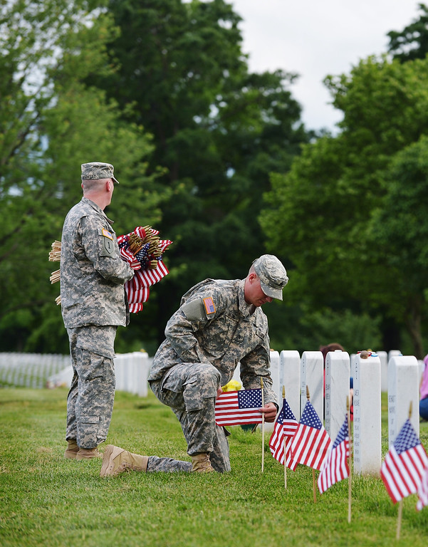 . A member of the Third US Infantry Regiment, The Old Guard, places a flag in front of a grave in Section 60 of Arlington National Cemetery on May 23, 2013 in Arlington, Virginia ahead of Memorial Day. Memorial Day is in honor of those who died while serving in the armed forces of the US. AFP PHOTO/Mandel NGAN/AFP/Getty Images