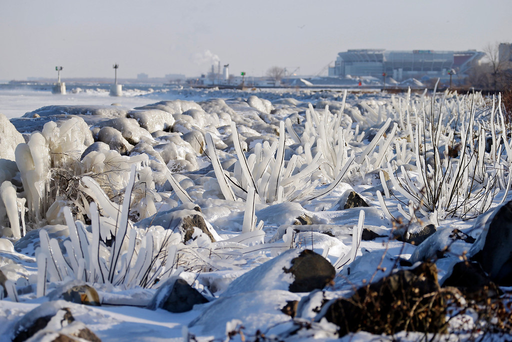 . Ice covers rocks and brush on the break wall at Edgewater Park in Cleveland Tuesday, Jan. 7, 2014. An official low of -11 degrees broke the 130-year-old record for the date as cold polar air spread from the Midwest to southern and eastern parts of the U.S. and eastern Canada. (AP Photo/Mark Duncan)
