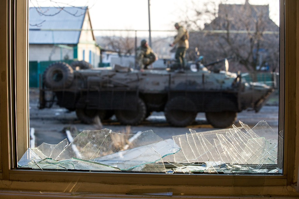 Description of . Ukrainian servicemen are seen standing on an Armoured Personnel Vehicle (APC) through a broken window in the village of Horlivka, Donetsk region, on February 4, 2015. Shelling at a hospital in east Ukraine killed four people on February 4 ahead of a visit to Kiev by US Secretary of State John Kerry that will see possible arms supplies high on the agenda. The latest deaths came as international pressure grew for an immediate halt to surging violence which has seen hundreds of civilians killed in recent weeks as pro-Russian rebels pushed into government-held territory. VOLODYMYR SHUVAYEV/AFP/Getty Images