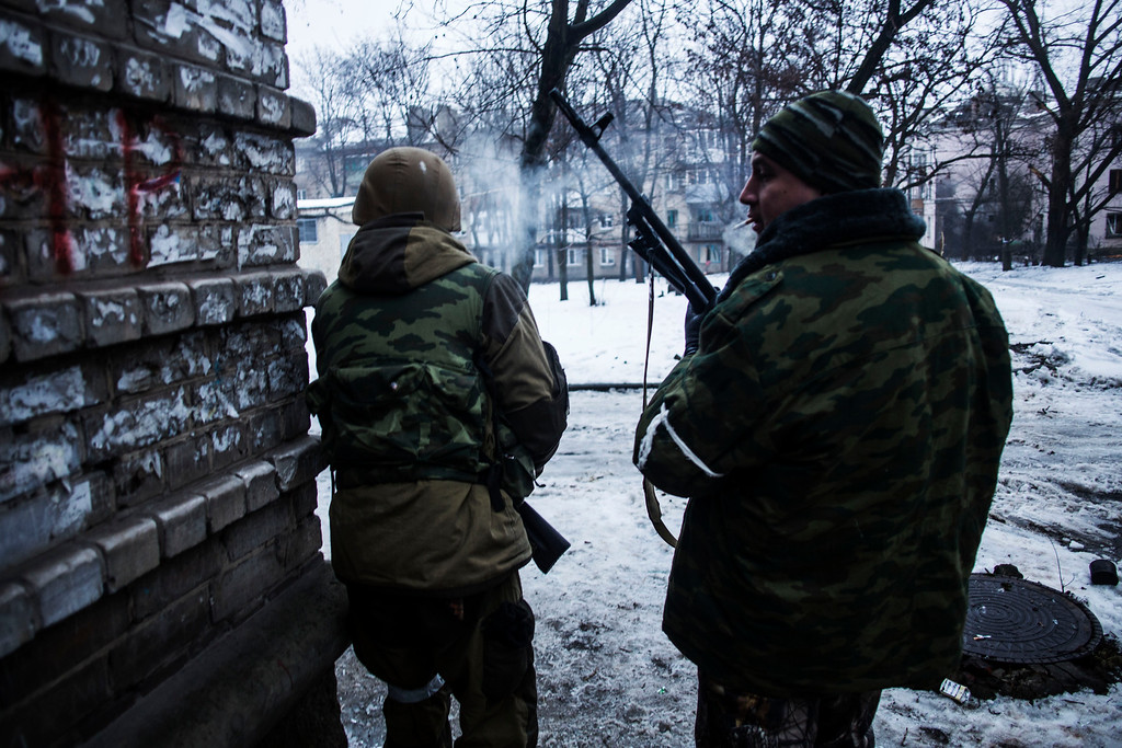 Description of . Russian backed separatist rebels advance, while looking for shelter, in the direction of the airport in the Kievsky district in Donetsk, Ukraine, Thursday, Jan. 22, 2015. A mortar shell hit a bus in the eastern Ukrainian rebel stronghold of Donetsk on Thursday, killing at least 13 people, the separatist leader in the city said. It was unclear immediately which side was responsible for the attack, which killed passengers instantly and blew out the windows of a nearby building. (AP Photo/Manu Brabo)