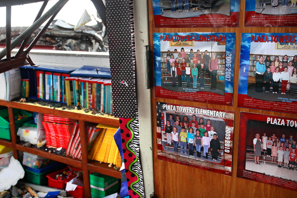 Description of . Class photos still decorate a classroom wall amid the wreckage of Plaza Towers Elementary School, where seven children were killed earlier in the week when a tornado hit Moore, Okla., Thursday, May 23, 2013. The huge tornado roared through the Oklahoma City suburb Monday, flattening entire neighborhoods and destroying the elementary school with a direct blow as children and teachers huddled against winds up to 200 mph. (AP Photo/Brennan Linsley)