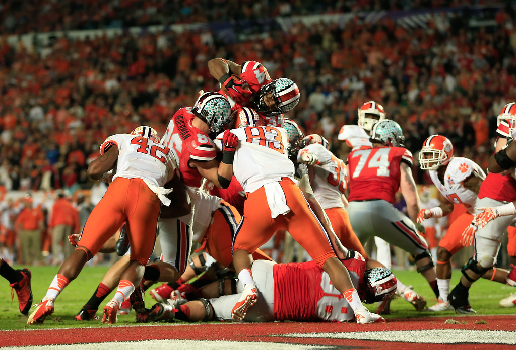 Description of . MIAMI GARDENS, FL - JANUARY 03:  Carlos Hyde #34 of the Ohio State Buckeyes jumps across the goal line for a touchdown in the third quarter against the Clemson Tigers during the Discover Orange Bowl at Sun Life Stadium on January 3, 2014 in Miami Gardens, Florida.  (Photo by Chris Trotman/Getty Images)