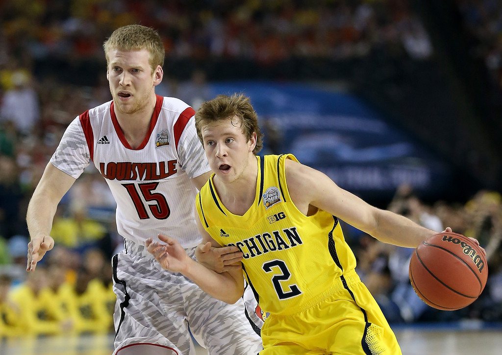 Description of . Spike Albrecht #2 of the Michigan Wolverines drives in the first half against Tim Henderson #15 of the Louisville Cardinals during the 2013 NCAA Men's Final Four Championship at the Georgia Dome on April 8, 2013 in Atlanta, Georgia.  (Photo by Streeter Lecka/Getty Images)