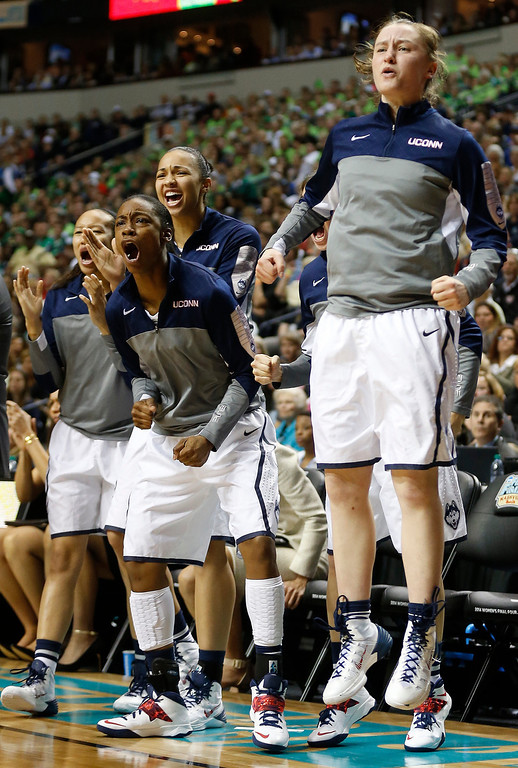 Description of . The Connecticut bench cheers against Notre Dame during the first half of the championship game in the Final Four of the NCAA women's college basketball tournament, Tuesday, April 8, 2014, in Nashville, Tenn. (AP Photo/John Bazemore)
