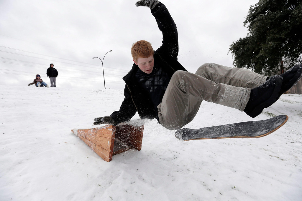 Description of . Matthew Eller, 15, catches air after sliding down a hill and jumping a ramp in Arlington, Texas, USA, 06 December 2013. A large ice storm causing travel problems and power outages moved through the Dallas, Texas area and across the midwest.  EPA/BRANDON WADE