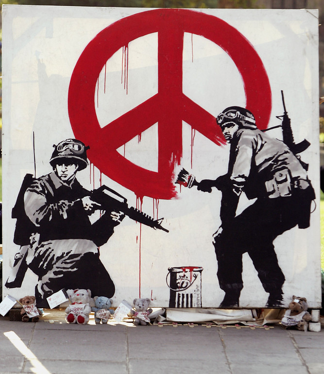 Description of . A artwork by British graffiti artist Banksy is seen as part of Brian Haw's peace protest outside the Houses of Parliament on May 11, 2006 in London.  The government won an appeal on monday against a ruling allowing Mr Haw to continue his five year long peace protest outside the Houses of Parliament.  (Photo by Bruno Vincent/Getty Images)