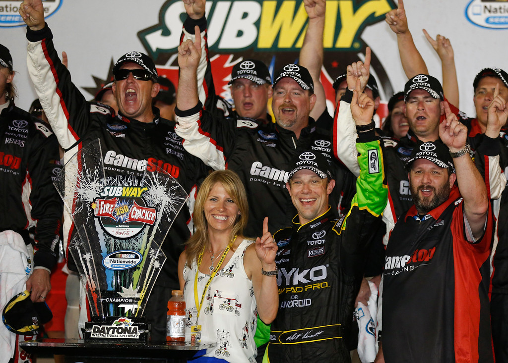Description of . Matt Kenseth, second from right, and his wife Katie, front left, celebrate with crew members in victory lane after winning the NASCAR Nationwide auto race at Daytona International Speedway, Friday, July 5, 2013, in Daytona Beach, Fla.  (AP Photo/Reinhold Matay)
