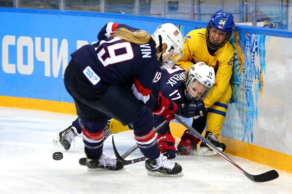Description of . Jocelyne Lamoureux #17 and Gigi Marvin #19 of the United States fight for a loose puck with Erika Grahm #24 of Sweden in the third period during the Women's Ice Hockey Playoffs Semifinal game on day ten of the Sochi 2014 Winter Olympics at Shayba Arena on February 17, 2014 in Sochi, Russia.  (Photo by Martin Rose/Getty Images)