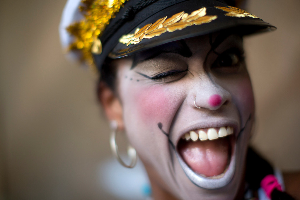 Description of . A woman smiles for a photo at the 'Carnaval na Central' carnival block parade, in central station, during pre-Carnival celebrations in Rio de Janeiro, Brazil, Saturday, Feb. 2, 2013. (AP Photo/Felipe Dana)