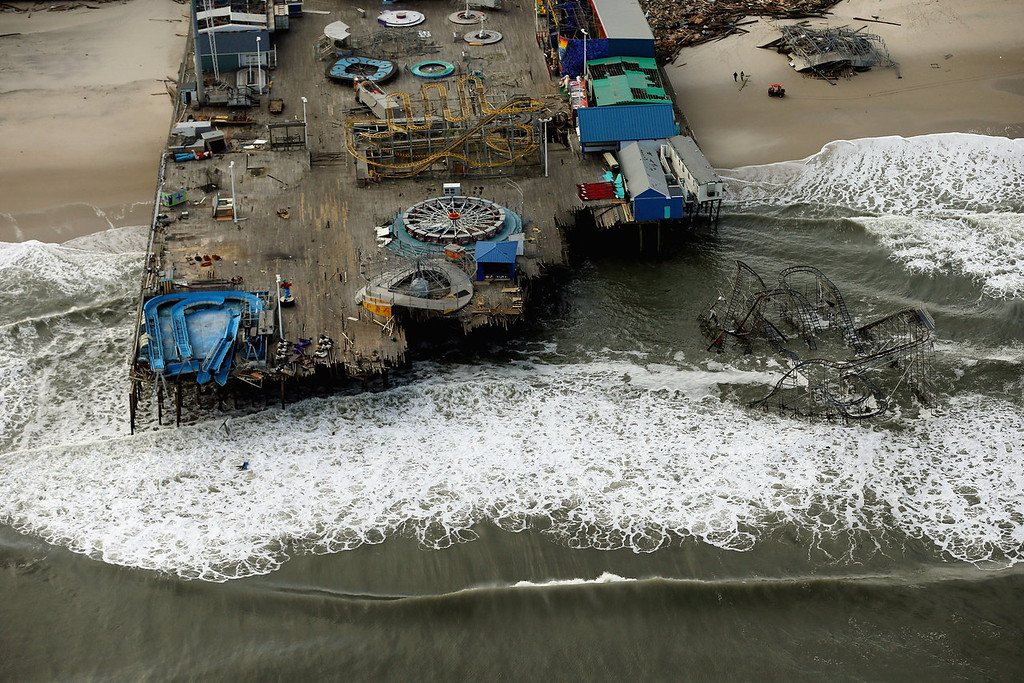 . Waves break in front of a destroyed amusement park wrecked by Superstorm Sandy on October 31, 2012 in Seaside Heights, New Jersey. At least 50 people were reportedly killed in the U.S. by Sandy with New Jersey suffering massive damage and power outages.   (Photo by Mario Tama/Getty Images)