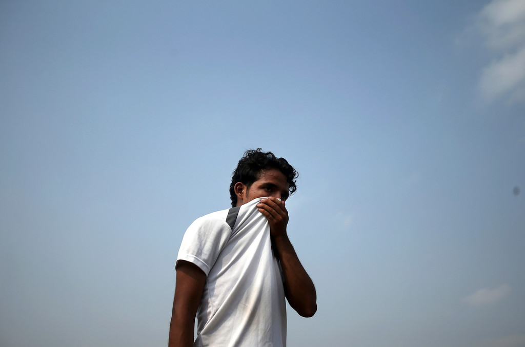 Description of . A man covers his nose to block out the smell of decomposing bodies as a truck transporting unclaimed bodies from the garment factory building that collapsed last week arrives for a mass burial, Wednesday May 1, 2013, in Dhaka, Bangladesh.  (AP Photo/Wong Maye-E)