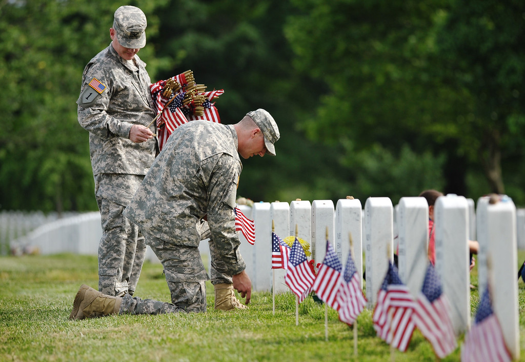 Description of . Members of the Third US Infantry Regiment, The Old Guard, place flags in front of graves in Section 60 of Arlington National Cemetery on May 23, 2013 in Arlington, Virginia ahead of Memorial Day.  AFP PHOTO/Mandel NGAN/AFP/Getty Images