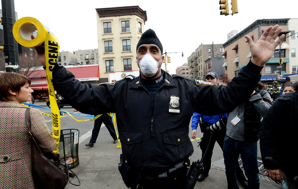 Description of . A police officer tries to push back the crowd of people near the scene where a group of buildings were damaged by fire and a possible explosion in Harlem, New York City, New York, USA, 12 March 2014.  EPA/JUSTIN LANE