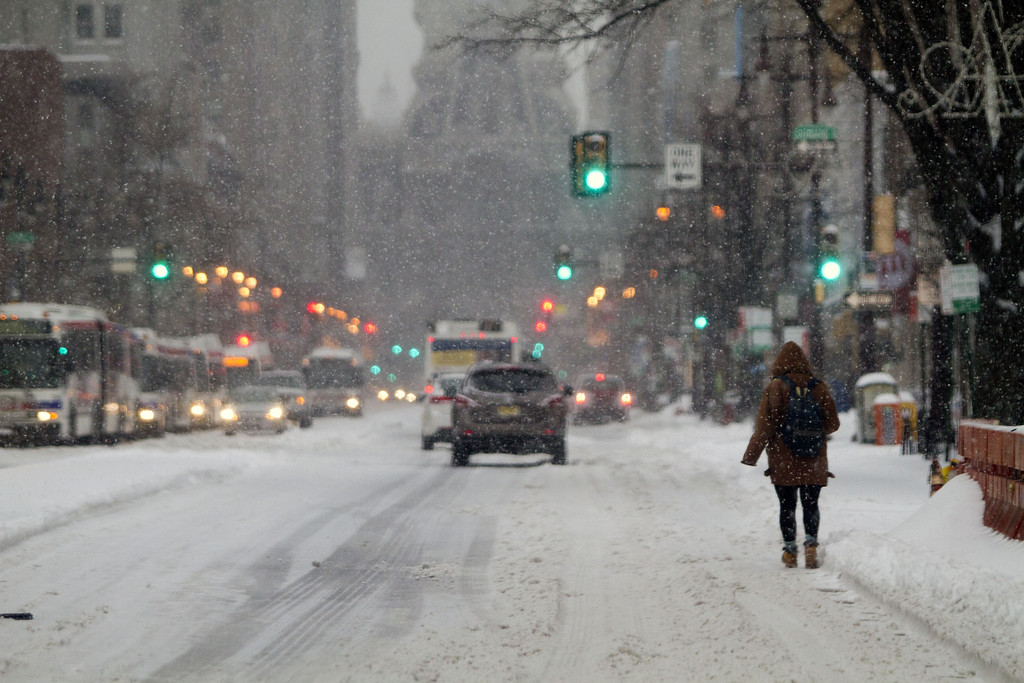 Description of . Residents walk through the snow covered streets on February 13, 2014 in Philadelphia, Pennsylvania. The east coast was hit with a winter snowstorm bringing sleet and snow. (Photo by Jessica Kourkounis/Getty Images)