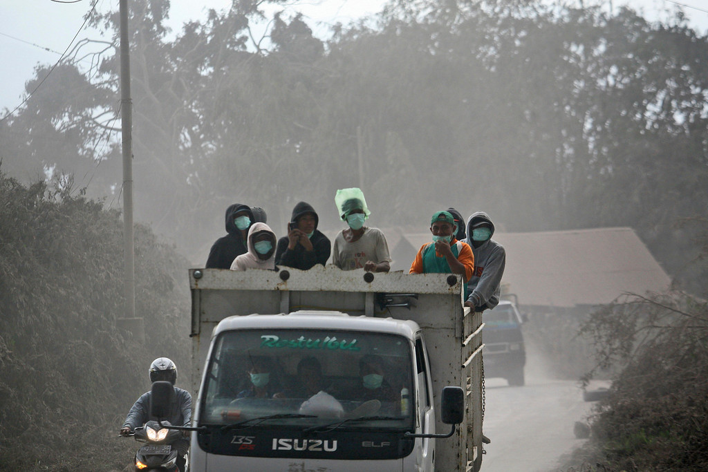 Description of . Vilagers ride on a truck on a road that has been covered with volcanic ash from the eruptions of Mount Sinabung in Sibintun, North Sumatra, Indonesia, Monday, Jan. 6, 2014. The volcano unleashed more clouds of searing gas avalanching down the mountain with a thunderous roar, forcing tens of thousands of people packed emergency shelters. (AP Photo/Binsar Bakkara)