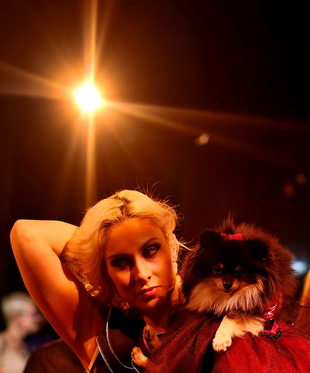Description of . Victoria Viscardi brushes back her hair while holding her dog Gia Marie, a Pomeranian breed, before the start of the New Yorkie Runway Doggie Fashion Show in New York February 7, 2013. REUTERS/Shannon Stapleton