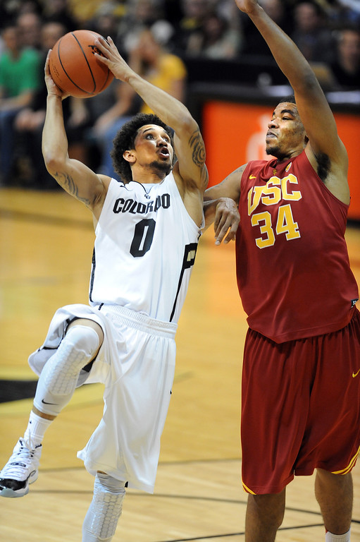 Description of . Askia Booker of CU shoots on Eric Wise of USC during the second half of the January 10, 2013 game in Boulder.   Cliff Grassmick/Daily Camera