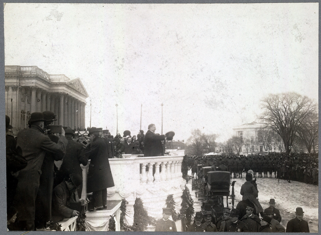 Description of . Side view of Taft on balustrade in the snow, with his top hat in hand, gesturing to crowd before him on the grounds of east front of Capitol, with photographers at left. (Photo from The Library of Congress)