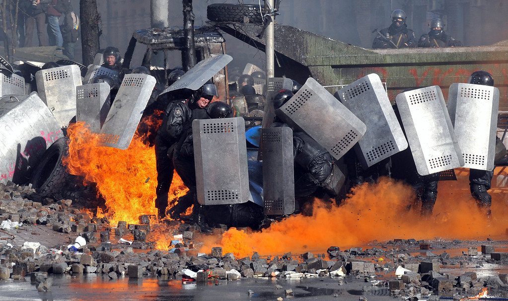 Description of . Anti-government protesters shield themselves during clashes with riot police in central Kiev on February 18, 2014. Five people died on February 18 as anti-government protesters clashed with security forces in central Kiev, a police spokeswoman said.