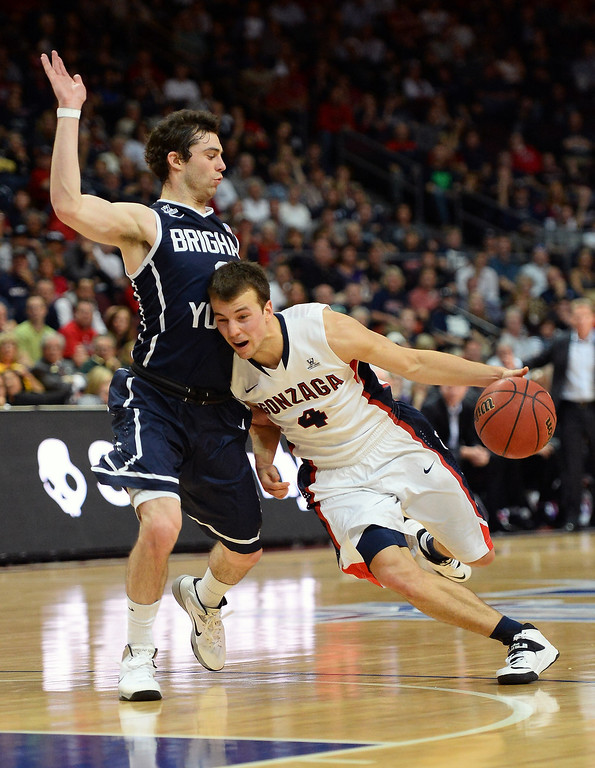 Description of . Kevin Pangos #4 of the Gonzaga Bulldogs drives against Matt Carlino #2 of the Brigham Young Cougars during the championship game of the West Coast Conference Basketball tournament at the Orleans Arena on March 11, 2014 in Las Vegas, Nevada.  (Photo by Ethan Miller/Getty Images)