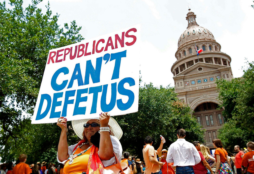 Description of . Lisa Hernandez of Corpus Christi, Texas holds a sign at a protest before the start of a special session of the Legislature in Austin, Texas July 1, 2013. When the Texas Legislature convenes on Monday for a second special session, the Republican majority will seek to do what it couldn't pull off in the first, when Democrat Wendy Davis stalled the measure for hours: Pass sweeping abortion restrictions.  REUTERS/Mike Stone
