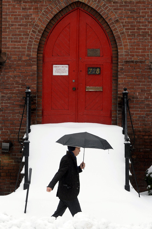 Description of . A pedestrian walks through thick snow while passing a church door in Washington DC, USA, 13 February 2014. The Washington DC area was pounded by a snowstorm, with accumulation expected to reach twelve inches in some areas, as the storm moved up the mid-Atlantic to the Northeast region of the US.  EPA/MICHAEL REYNOLDS