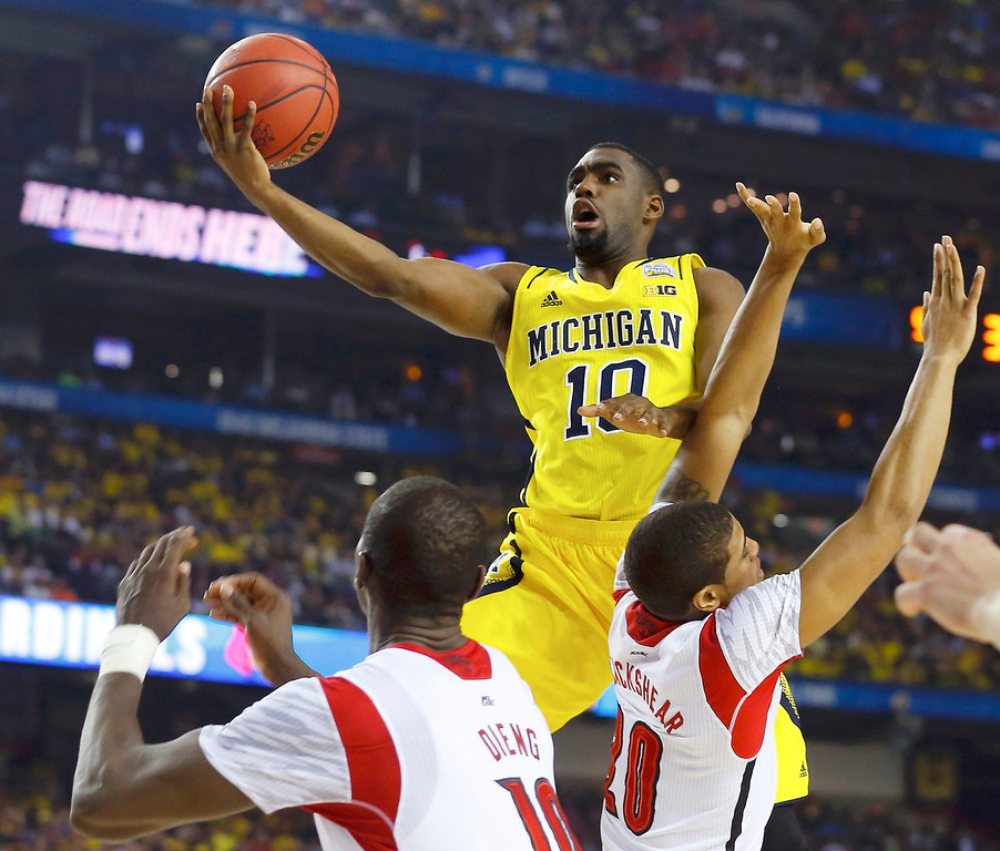 Description of . Michigan Wolverines guard Tim Hardaway Jr. lays in the ball over Louisville Cardinals center Gorgui Dieng (L) and guard/forward Wayne Blackshear during the first half of their NCAA men's Final Four championship basketball game in Atlanta, Georgia April 8, 2013. REUTERS/Chris Keane