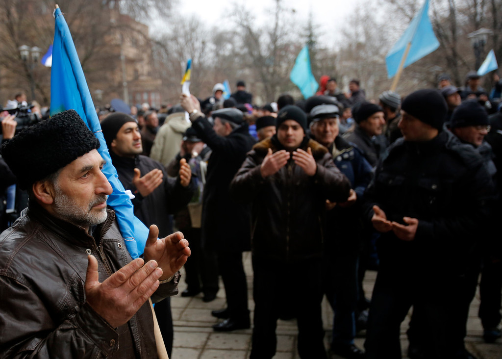 Description of . Crimean Tatars pray during a protest in front of a local government building in Simferopol, Crimea, Ukraine, Wednesday, Feb. 26, 2014. More than 10,000 Muslim Tatars rallied in support of the interim government. That group clashed with a smaller pro-Russian rally nearby. Fistfights broke out between pro- and anti-Russian demonstrators in Ukraine's strategic Crimea region on Wednesday as Russian President Vladimir Putin ordered massive military exercises just across the border. (AP Photo/Darko Vojinovic)