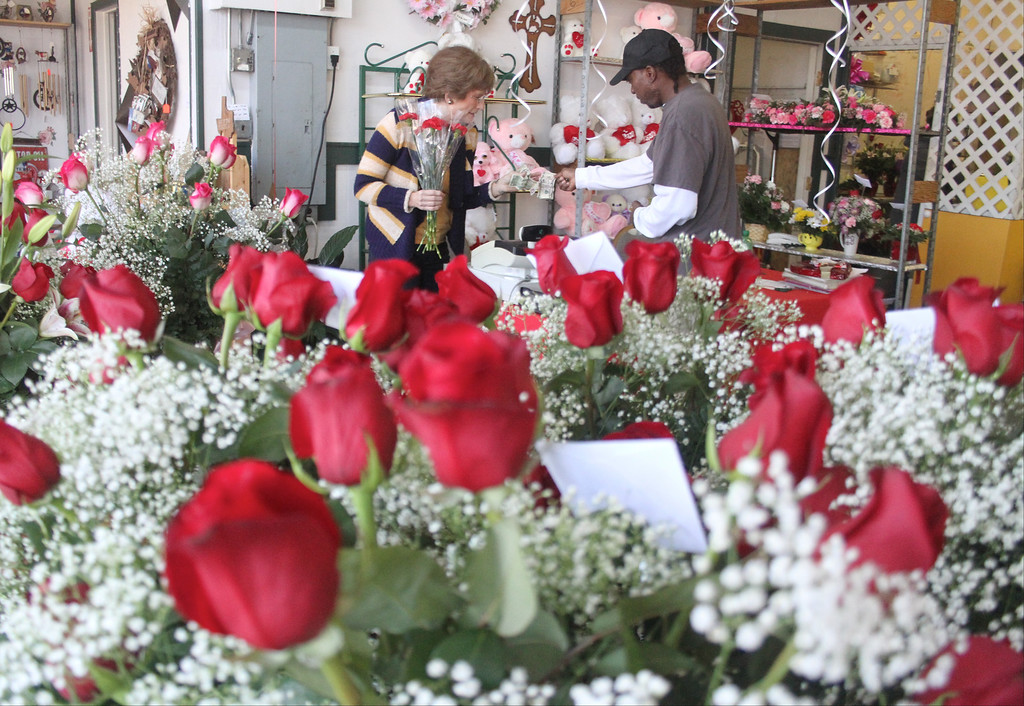 Description of . Wanda Smith, left, gives Clarence Coleman a bouquet of red roses he ordered for Valentine's Day at Flowers Texas Style on Thursday, Feb. 14, 2013, in Conroe, Texas. Workers at the shop estimate they will have assembled more than 700 arrangements before the end of Valentine's Day. (AP Photo/ The Courier, Jason Fochtman)