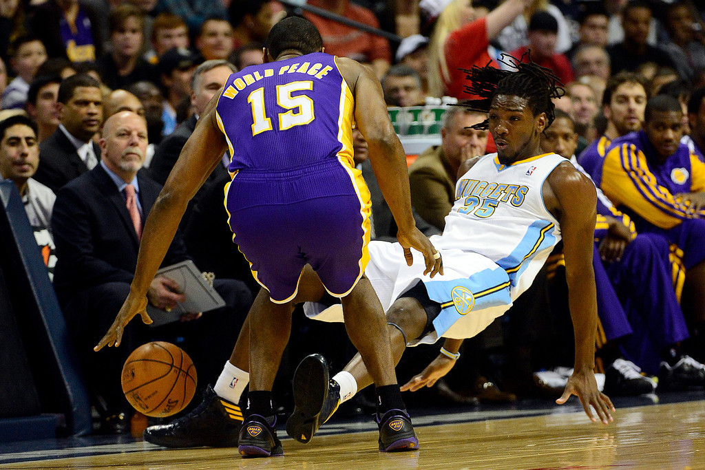 Description of . Denver Nuggets small forward Kenneth Faried (35) hits the deck after taking contact from Los Angeles Lakers small forward Metta World Peace (15) during the first half at the Pepsi Center on Wednesday, December 26, 2012. AAron Ontiveroz, The Denver Post
