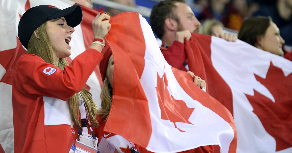 Description of . Canada's fans celebrate at the end of the Women's Ice Hockey semifinal match Canada vs Switzerland at the Shayba Arena during the Sochi Winter Olympics on February 17, 2014. Canada won 3-1.   ALEXANDER NEMENOV/AFP/Getty Images