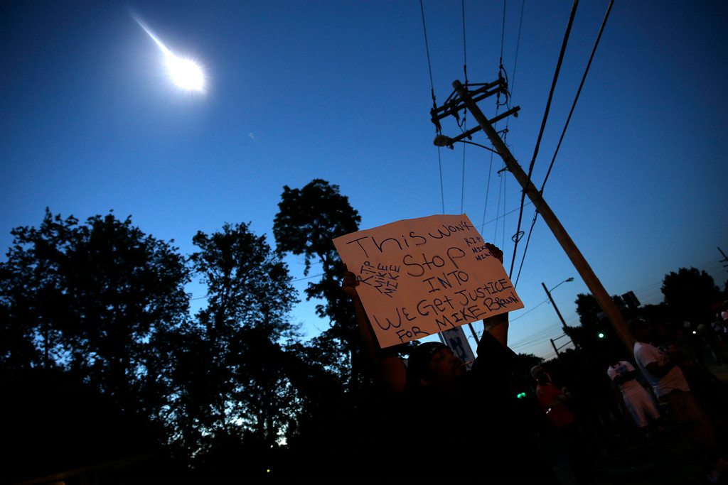 Description of . A protester holds up a sign as a police helicopter circles overhead Wednesday, Aug. 13, 2014, in Ferguson, Mo. Protests in the St. Louis suburb rocked by racial unrest since a white police officer shot an unarmed black teenager to death turned violent Wednesday night, with some people lobbing Molotov cocktails and other objects at police who responded with smoke bombs and tear gas to disperse the crowd. (AP Photo/Jeff Roberson)