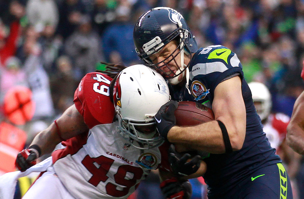 Description of . Seattle Seahawks tight end Zach Miller (86) is hit by Arizona Cardinals strong safety Rashad Johnson (49) as he scores on a 24-yard touchdown reception during the second quarter of an NFL football game in Seattle, Sunday, Dec. 9, 2012. (AP Photo/Stephen Brashear)