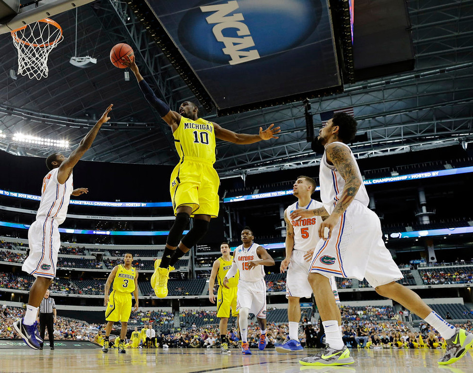 Description of . Michigan\'s Tim Hardaway Jr. (10) shoots past Florida\'s Kenny Boynton (1) and Mike Rosario (3) during the first half of a regional final game in the NCAA college basketball tournament, Sunday, March 31, 2013, in Arlington, Texas. Florida\'s Casey Prather (24) looks on. (AP Photo/Tony Gutierrez)