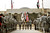 U.S. Military personnel holding the US flag, Iraq flag, and the US Forces Iraq colors march during a casing ceremony where the United States Forces- Iraq flag was retired, signifying the departure of United States troops from Iraq, at the former Sather Air Base on December 15, 2011 in Baghdad, Iraq. United States forces were scheduled to entirely depart Iraq by December 31.  (Photo by Mario Tama/Getty Images)