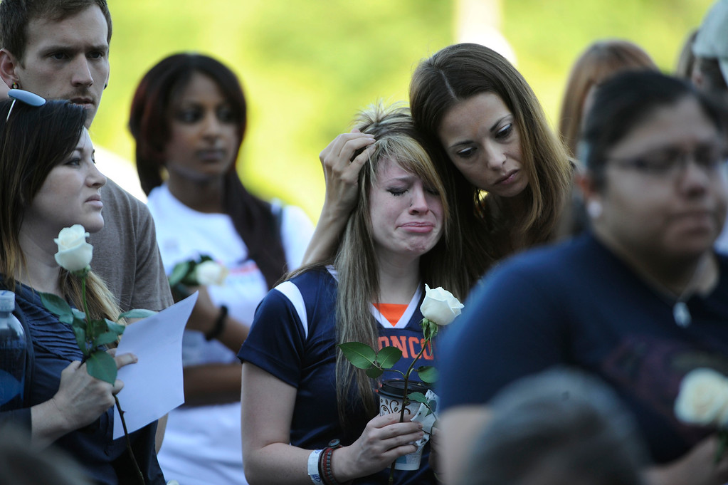 Description of . AURORA, CO - JULY 20:  Jansen Young, 22, center, (holding rose) is comforted by a friend during the 7/20 Day of Remembrance 2013 at the Aurora Municipal Center Saturday morning, July 20, 2013. Over 200 people attended the service in honor of the 12 people killed and over 60 people injured in last years Aurora theater shooting. Young's boyfriend, Jonathan Blunk was killed in the attack covering and protecting Young July 20, 2012. The service included prayer, songs and speeches from local officials and the Governor of Colorado, John Hickenlooper. (Photo By Andy Cross/The Denver Post)