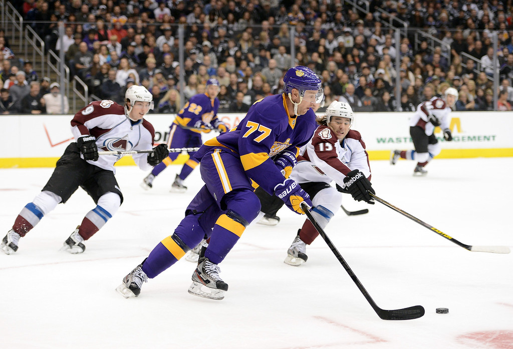 Description of . LOS ANGELES, CA - FEBRUARY 23:  Jeff Carter #77 of the Los Angeles Kings clears his zone as P.A. Parenteau #15 and Matt Duchene #9 of the Colorado Avalanche chase at Staples Center on February 23, 2013 in Los Angeles, California.  (Photo by Harry How/Getty Images)