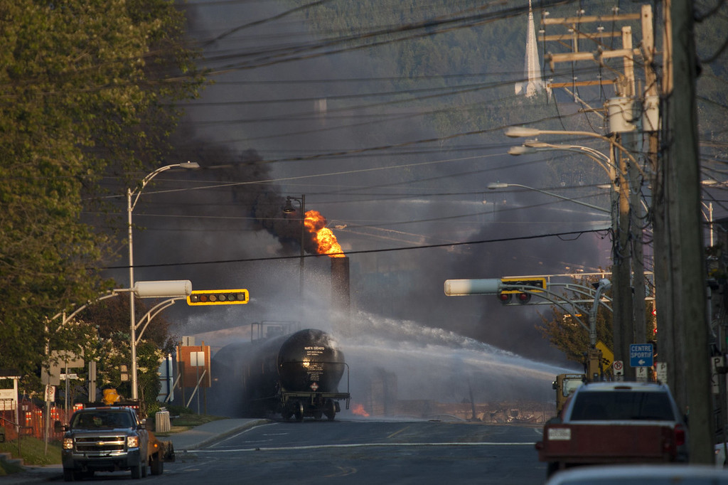 Description of . Firefighters douse a blaze after a freight train loaded with oil derailed in Lac Megantic in Canada\'s Quebec province on July 6, 2013, sparking explosions that engulfed about 30 buildings in fire. At least one person has been killed and some 2,000 people forced from their homes.  François Laplante-Delagrave/AFP/Getty Images
