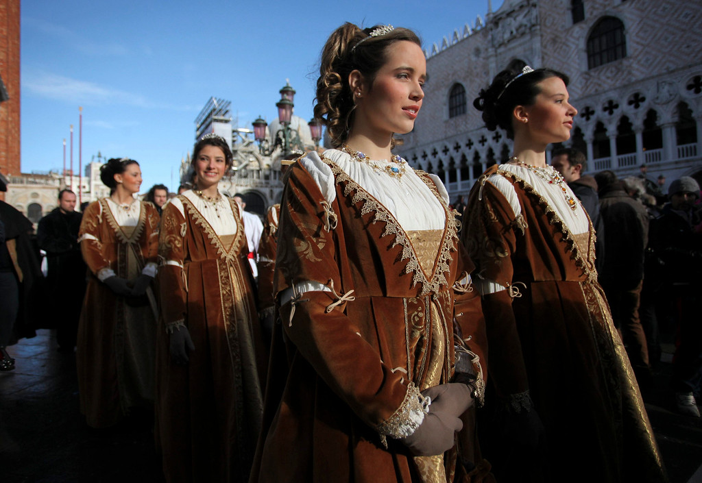 Description of . Women dressed in traditional costumes pose during the Venetian Carnival in Saint Mark's square in Venice February 3, 2013.  REUTERS/Manuel Silvestri