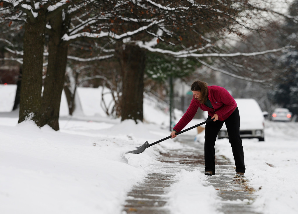 Description of . Amy Davison shovels snow in her neighborhood following a winter storm Friday, Dec. 6, 2013, in Indianapolis. Several inches of snow fell on central and southern Indiana, making driving treacherous and leading to at least two fatal crashes. (AP Photo/Darron Cummings)